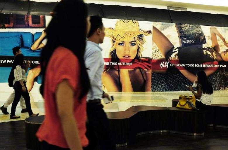 People walk in front of a billboard of a new store at a mall in Jakarta, September 4, 2013. REUTERS/Beawiharta