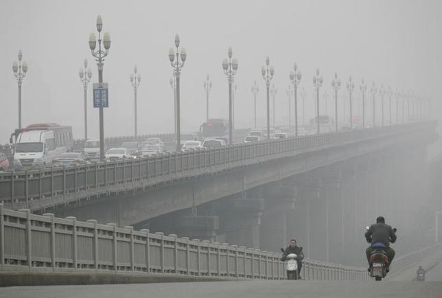 People ride along a bridge on a smoggy day in Nanjing, Jiangsu province, January 18, 2014. REUTERS/China Daily