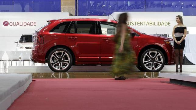 A model walks past a 2011 Ford Edge at the 26th International Automobile Trade Show in Sao Paulo October 25, 2010. REUTERS/Paulo Whitaker