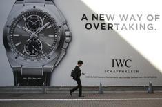 Человек проходит мимо рекламы часов в Токио 13 ноября 2013 года. Любители предметов роскоши будут тратить 880 миллиардов евро ($1,2 триллиона) в год на покупки к 2020 году - на 20 процентов больше, чем они тратят на аналогичные вещи сейчас, говорится в исследовании. REUTERS/Yuya Shino