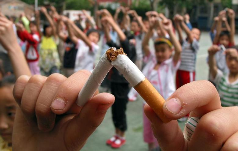 Pupils break cigarettes as a gesture showing their determinations of non-smoking at an elementary school of Jinan, the capital eastern China's Shandong province May 29, 2006. REUTERS/Stringer
