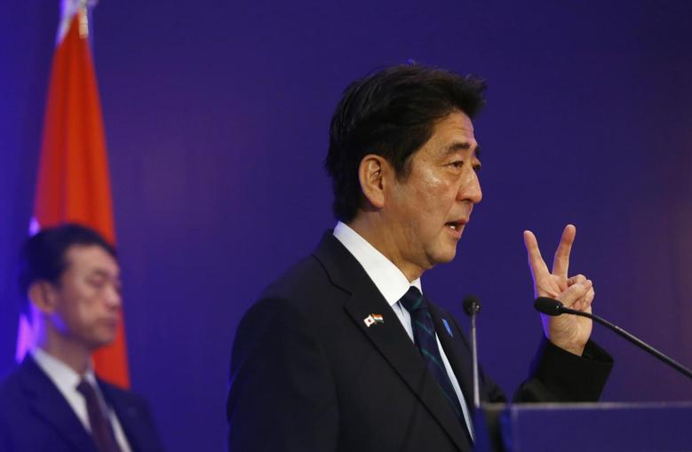 Japan's Prime Minister Shinzo Abe shows a sign as he speaks at a business meeting organised by Confederation of Indian Industry (CII) in New Delhi January 25, 2014. REUTERS/Anindito Mukherjee