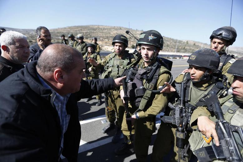 A Palestinian man argues with Israeli soldiers as they guard near the site of a fatal shooting incident next to the Palestinian village of Ein Sariya, north of the West Bank city of Ramallah January 29, 2014. REUTERS/Mohamad Torokman