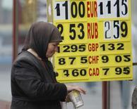 Женщина просит милостыню у пункта обмена валют в Киеве 24 сентября 2013 года. Временный глава правительства Украины рассчитывает, что отставка премьер-министра Николая Азарова на волне массовых протестов не задержит очередной транш обещанного Москвой кредита на $15 миллиардов. REUTERS/Gleb Garanich