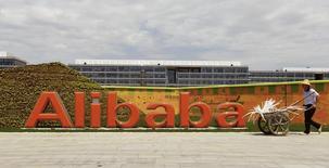 Funcionário passa pelo logotipo do Alibaba em sua sede em Hangzhou. O impressionante crescimento do Alibaba pode estar arrefecendo, mas só levemente. 24/08/2013 REUTERS/China Daily
