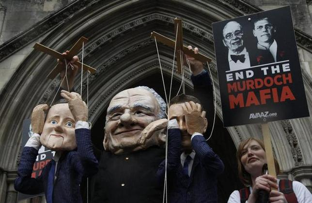 A demonstrator dressed as Rupert Murdoch protests outside the High Court in central London April 25, 2012. REUTERS/Suzanne Plunkett/Files