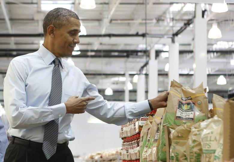 U.S. President Barack Obama holds up a bag of chips as he tours Costco Wholesale in Woodmore Towne Centre in Lanham, Maryland January 29, 2014. REUTERS/Yuri Gripas