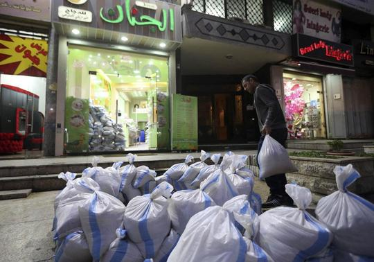 A man moves sandbags towards a shop as protection from future explosions at a stronghold of the Shi'ite group Hezbollah in the southern suburbs of the Lebanese capital Beirut January 28, 2014. REUTERS-Hasan Shaaban