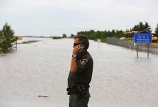 A Fish and Game officer talks on his mobile phone about rescuing animals in the flood in High River, Alberta, June 29, 2013. REUTERS/Todd Korol