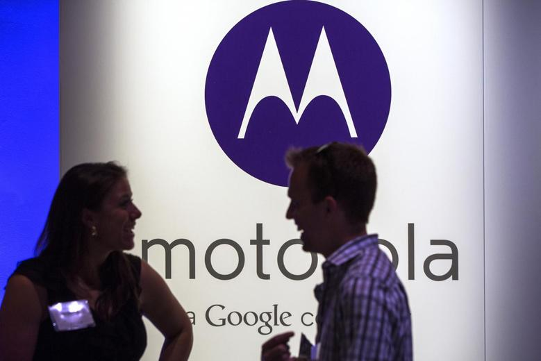 A man and woman laugh in front of a Motorola logo at a launch event for Motorola's new Moto X phone in New York, August 1, 2013. REUTERS/Lucas Jackson/Files