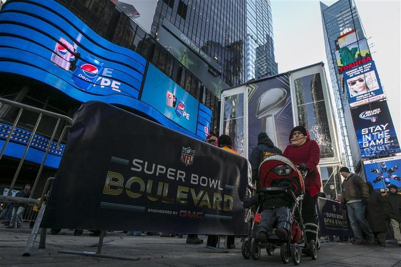 A woman walks through Times Square which has been transformed into Super Bowl Boulevard ahead of Super Bowl XLVIII in New York January 29, 2014. REUTERS/Brendan McDermid