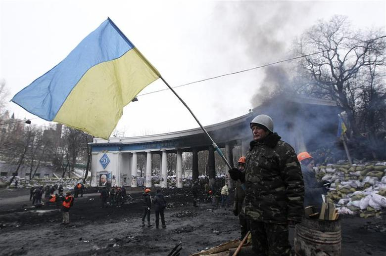 An anti-government protester waves a Ukranian flag near barricades at the site of clashes with riot police in Kiev January 28, 2014. REUTERS/Valentyn Ogirenko