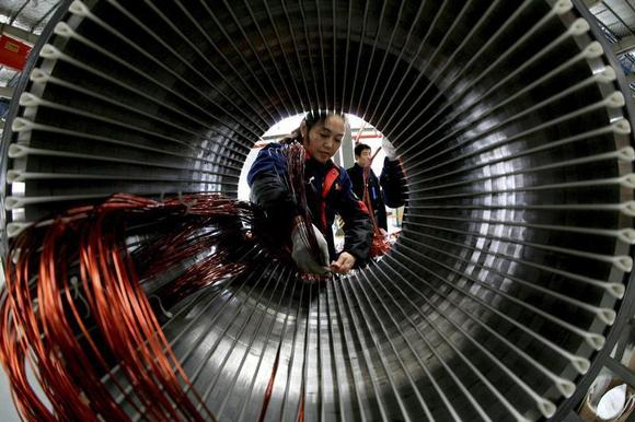A worker assembles a generator at a factory in Hefei, Anhui province November 2, 2013. REUTERS/China Daily/Files