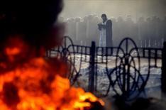 Священник читает молитву перед рядами сотрудников правоохранительных органов во время столкновений с оппозицией в Киеве 25 января 2014 года. Администрация президента США Барака Обамы готовит финансовые санкции, которые могут быть применены как к украинским чиновникам, так и к лидерам протеста в случае эскалации насилия на фоне охватившего страну политического кризиса, сообщили сотрудники Конгресса. REUTERS/Antti Aimo-Koivisto/Lehtikuva