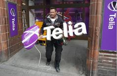 Мужчина готовится установить новый логотип TeliaSonera в Стокгольме 12 мая 2011 года. Скандинавский телекоммуникационный оператор TeliaSonera прогнозирует, что выручка и рентабельность компании сохранятся на уровне 2013 года после того, как итоги четвертого квартала оказались хуже прогнозов. REUTERS/Bob Strong