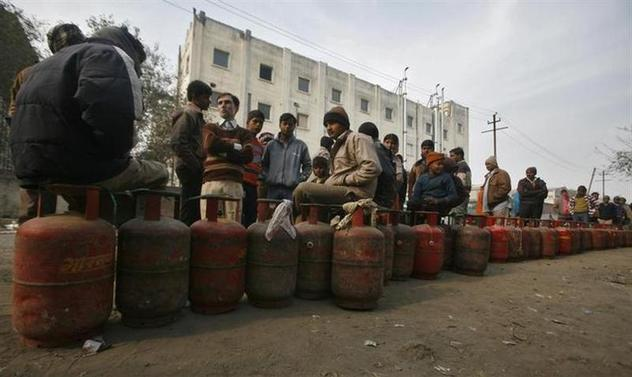 People with their empty cooking gas cylinders wait for a truck carrying replacements on a street at Noida in Uttar Pradesh January 27, 2011. REUTERS/Parivartan Sharma/Files