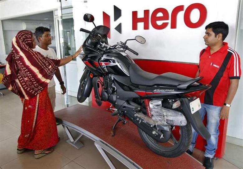 Customers look at a Hero MotoCorp Karizma motorbike at a Hero MotoCorp showroom in Ahmedabad April 26, 2013. REUTERS/Amit Dave/Files