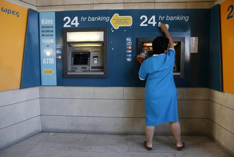 A cleaning lady wipes dust off an ATM outside a branch of the Bank of Cyprus in Nicosia March 28, 2013. REUTERS/Yannis Behrakis