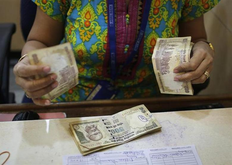 A cashier counts rupees inside a bank in Mumbai December 6, 2013. REUTERS/Danish Siddiqui/Files