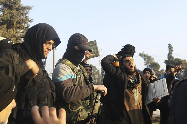 Fighters from the Islamic State in Iraq and the Levant (ISIL) try to calm civilians demonstrating against the rebel infighting in Aleppo January 6, 2014. REUTERS/Jalal Alhalabi