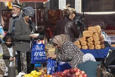 Люди на уличном рынке в Душанбе 1 ноября 2013 года. Центробанк Таджикистана надеется удержать инфляцию в этом году ниже 7,5 процента в расчёте на приток валюты от работающих за рубежом и на относительную дешевизну беспошлинных нефтепродуктов из России, которой продлил аренду военной базы на 29 лет. REUTERS/Nozim Kalandarov