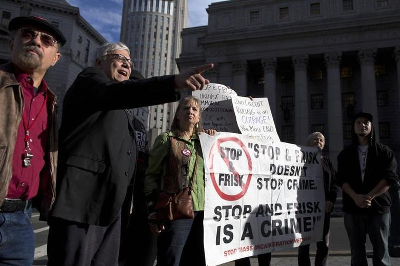 People hold signs protesting against the Stop-and-Frisk program, at a news conference outside the Federal Court in New York November 1, 2013. REUTERS/Andrew Kelly