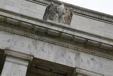La entrada del edificio de la Reserva Federal en Washington, jul 31 2013. La reciente turbulencia en los mercados emergentes no evitará que la Reserva Federal de Estados Unidos siga recortando sus compras mensuales de bonos a un ritmo de 10.000 millones de dólares en cada uno de sus próximos encuentros de política monetaria, para cerrar el programa a fines de año, mostró un sondeo de Reuters. REUTERS/Jonathan Ernst
