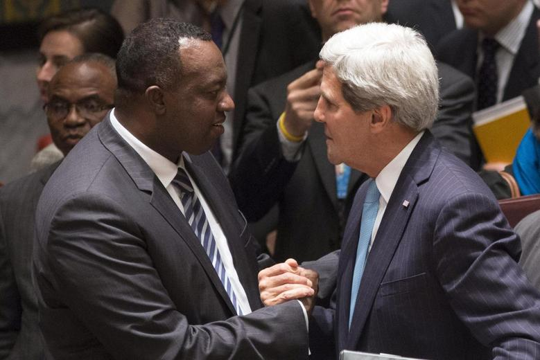 Rwanda Ambassador to the United Nations Eugene-Richard Gasana (L) greets U.S. Secretary of State John Kerry after taking part in a United Nations Security Council meeting where the council voted unanimously to approve a resolution eradicating Syria's chemical arsenal in New York September 27, 2013. REUTERS/Adrees Latif