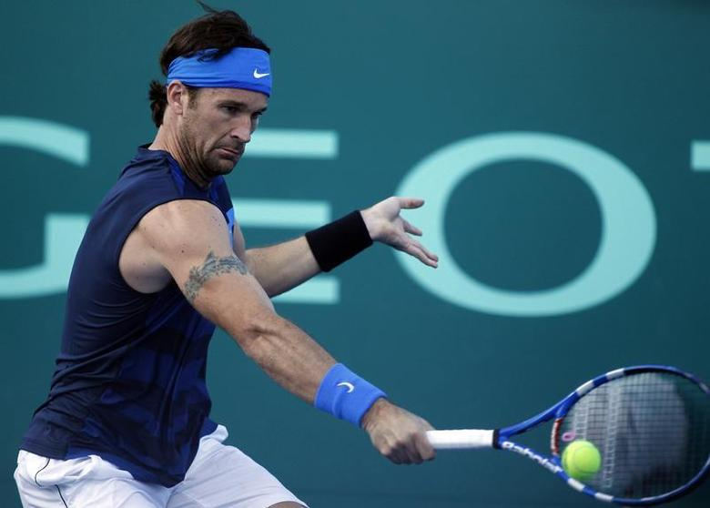 Carlos Moya of Spain returns the ball during his farewell exhibition tennis match against Guillermo Canas of Argentina in Buenos Aires, December 19, 2010. REUTERS/Marcos Brindicci