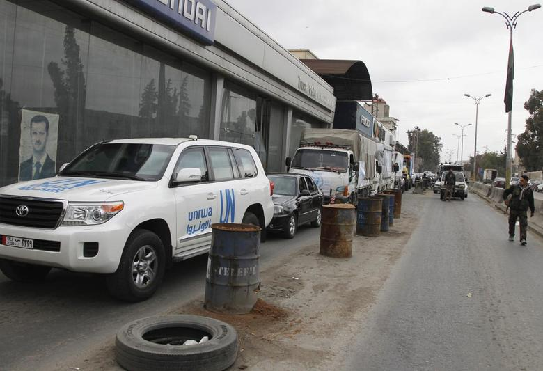 Trucks carrying food aid from UNRWA, enter a checkpoint manned by forces loyal to Syria's President Bashar al-Assad, as they make their way to the besieged camp of al-Yarmouk, south of Damascus, which is controlled by opposition fighters, January 13, 2014. REUTERS/Khaled al-Hariri