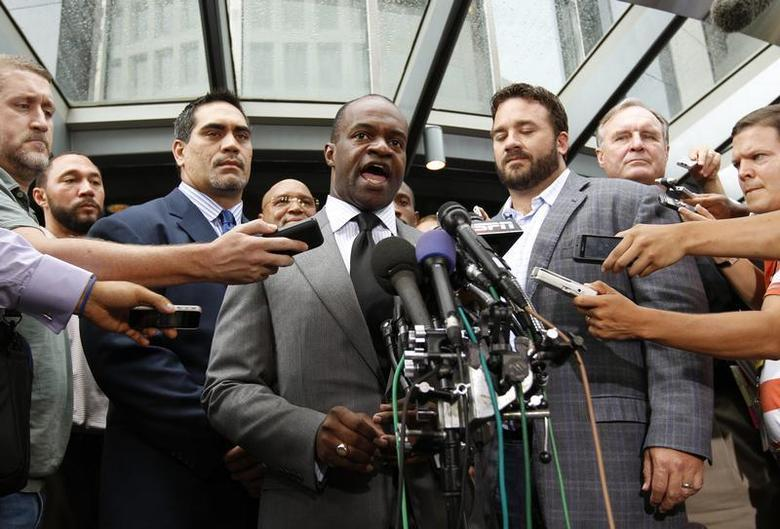 Executive director of the NFL Players Association DeMaurice Smith (C) speaks outside the NFL Players Association Headquarters in Washington July 25, 2011. REUTERS/Kevin Lamarque