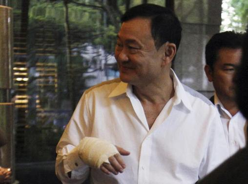 Thailand's former prime minister Thaksin Shinawatra sports a bandaged hand as he leaves a meeting at a hotel in Singapore January 27, 2014. REUTERS/Edgar Su