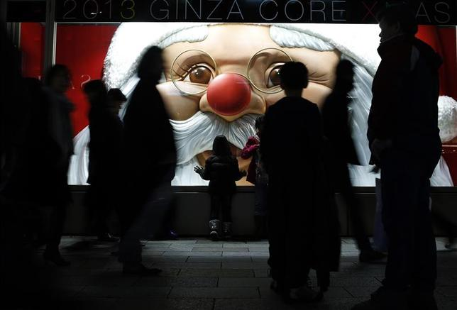 A child looks at a luxury brand store window with a Santa Claus display as people walk past at Ginza shopping district in Tokyo December 20, 2013. REUTERS/Yuya Shino