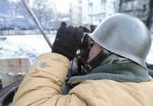 """Демонстрант смотрит в бинокль на баррикаде, возведенной антиправительственными активистами в ходе столкновений с милицией в центре Киева. Фото от 30 января 2014 года. Минобороны охваченной уличным противостоянием Украины в пятницу повторило, что армия останется вне конфликта, хотя часть высокопоставленных военных ждёт от верховного главнокомандующего, президента Виктора Януковича """"неотложных мер"""". REUTERS/Konstantin Chernichkin"""