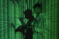 """Изображение человека с ноутбуком, на которого спроецирован бинарный код, в Варшаве 24 июня 2013 года. Хакеры атаковали небольших ритейлеров в 11 странах, включая Россию, украв данные с 49.000 платежных карт при помощи вирусной программы, известной как """"Чубакка"""", сообщила исследовательская фирма. REUTERS/Kacper Pempel"""