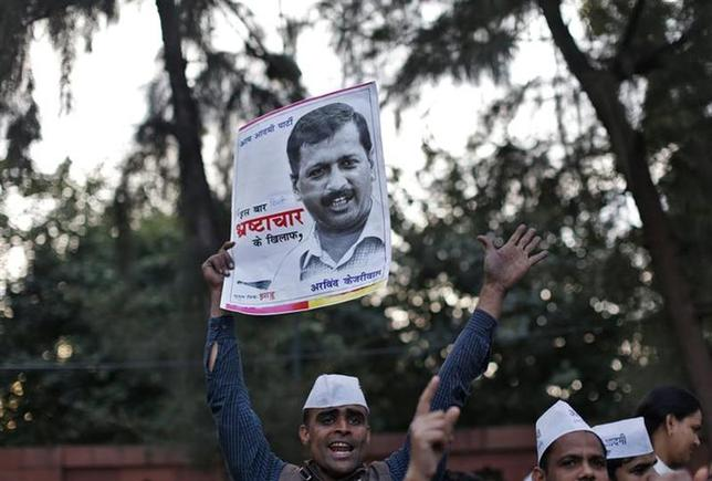 A supporter of Aam Aadmi (Common Man) Party (AAP) holds a portrait of Delhi's chief minister Arvind Kejriwal during a protest in New Delhi January 20, 2014. REUTERS/Ahmad Masood/Files