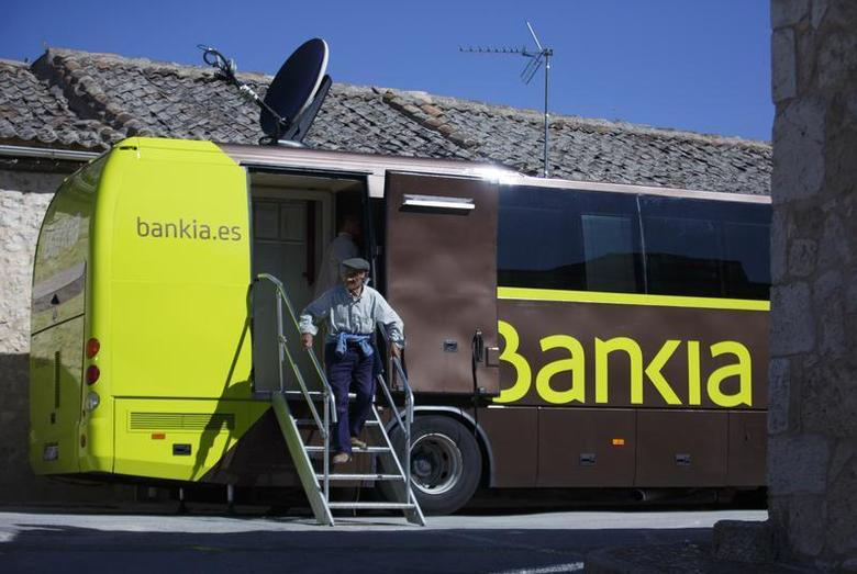 A customer steps off a bank bus during its monthly call on customers in the village of Maderuelo, central Spain, June 4, 2013. REUTERS/Sergio Perez