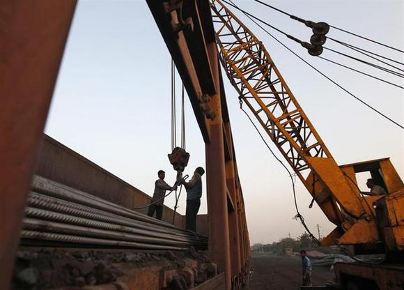 Workers prepare to unload steel rods with a crane from a goods train at a railway yard in Ahmedabad January 8, 2014. REUTERS/Amit Dave/Files