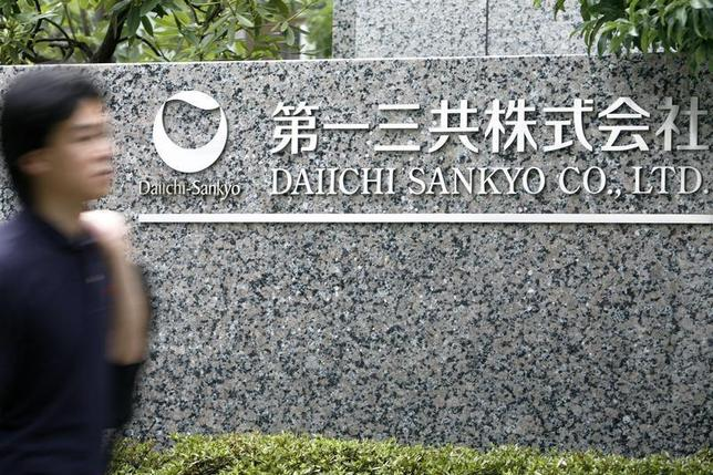 A man walks past a sign of Japanese pharmaceutical company Daiichi Sankyo Co., Ltd. at the company's head office in Tokyo July 17, 2009. REUTERS/Stringer
