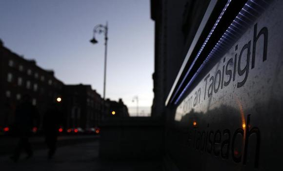 The setting sun is seen in a sign outside Government Buildings in Dublin December 5, 2011. REUTERS/Cathal McNaughton