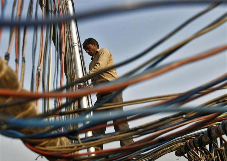An electrician installs power cables outside Parliament building in New Delhi December 10, 2013. REUTERS/Anindito Mukherjee/Files
