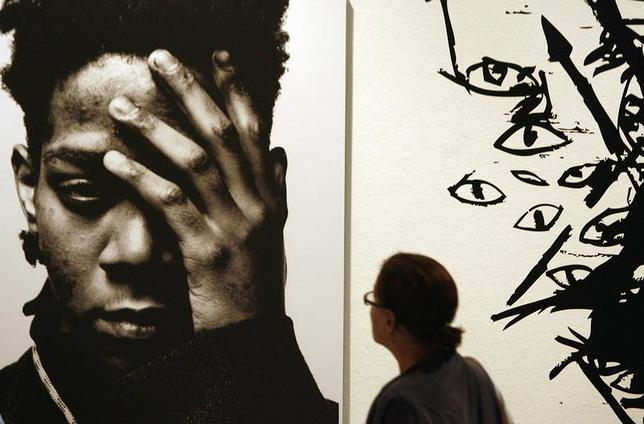 A woman looks at a work by late Haitian-American Jean-Michel Basquiat at an exhibition in Milan September 19, 2006. REUTERS/Stefano Rellandini