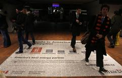 Commuters walk over an advertisement promoting Canada as a preferable oil provider for America at a metro station in Washington January 29, 2014. REUTERS/Yuri Gripas