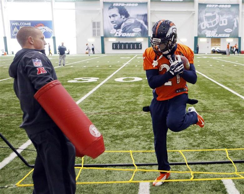 Denver Broncos running back Knowshon Moreno (R) runs a drill as an assistant stands by during their practice session for the Super Bowl at the New York Jets Training Center in Florham Park, New Jersey January 30, 2014. REUTERS/Ray Stubblebine