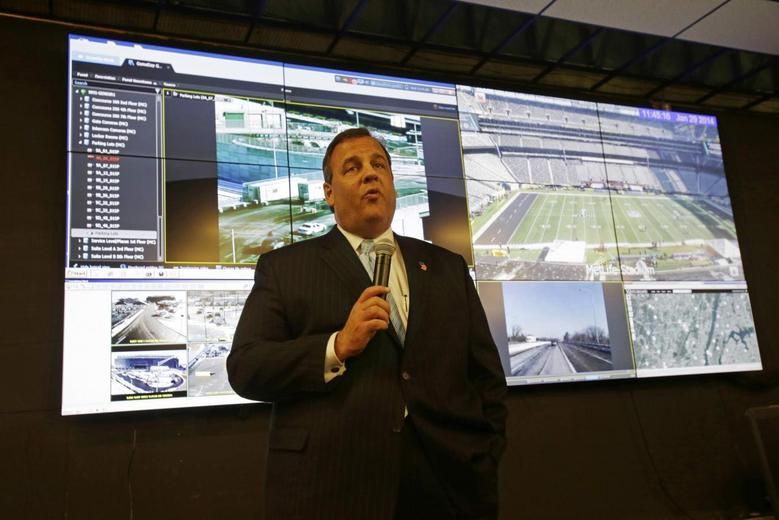 New Jersey Gov. Chris Christie speaks in front of a group of monitors as he visits the Super Bowl security operations center in East Rutherford, New Jersey January 29, 2014. REUTERS/Mel Evans/Pool