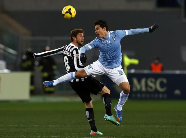 Lazio's Anderson Hernanes (R) jumps for the ball with Juventus' Claudio Marchisio during their Italian Serie A soccer match at the Olympic stadium in Rome January 25, 2014. REUTERS/Alessandro Bianchi