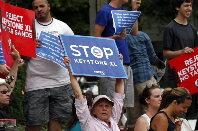 Protesters rally about the Keystone XL oil pipeline along U.S. President Barack Obama's motorcade as he arrives at the Jefferson Hotel in Washington July 11, 2013. REUTERS/Yuri Gripas