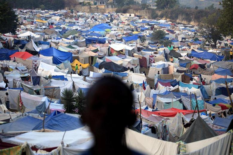 A boy stands at a makeshift camp on the grounds of the Petionville Golf Course in Port-au-Prince, Haiti in this January 26, 2010 file photo. REUTERS/Carlos Barria/Files