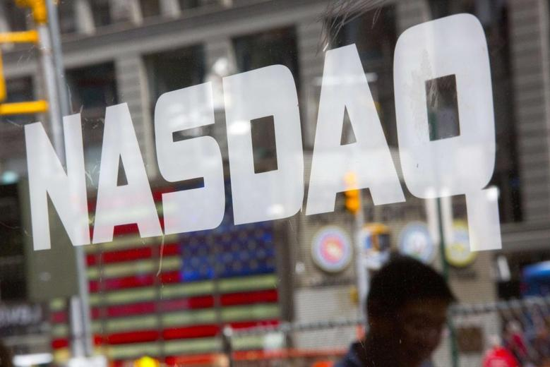 A man walks past the Nasdaq MarketSite in New York's Times Square in this August 23, 2013 file photo. REUTERS/Andrew Kelly/Files