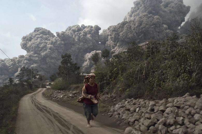 A villager run as Mount Sinabung erupt at Sigarang-Garang village in Karo district, Indonesia's North Sumatra province, February 1, 2014. REUTERS/Stringer